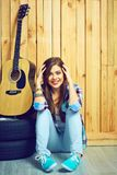 Muchacha adolescente sonriente del inconformista que se sienta en piso Foto de archivo