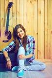 Muchacha adolescente sonriente del inconformista que se sienta en piso Fotografía de archivo