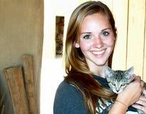 Muchacha adolescente sonriente del primer que sostiene un gatito Imagen de archivo libre de regalías
