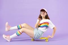 Muchacha adolescente sonriente en la ropa viva, vidrios que se sientan en el monopat?n, control algo, se?alando la mano de la c?m foto de archivo libre de regalías