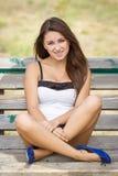Muchacha adolescente sonriente en un banco Fotografía de archivo