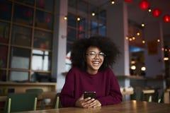 Muchacha adolescente sonriente encantadora que se divierte durante tiempo libre en el café dentro que charla con el amigo Imagen de archivo