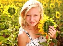 Muchacha adolescente sonriente feliz con el girasol en campo del verano Imagen de archivo