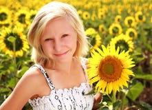 Muchacha adolescente sonriente feliz con el girasol en campo del verano Fotografía de archivo