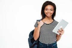 Muchacha adolescente sonriente feliz con la mochila que sostiene la tableta de la PC Imagenes de archivo