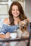 Muchacha adolescente sonriente feliz que sostiene el pequeño perro Foto de archivo libre de regalías