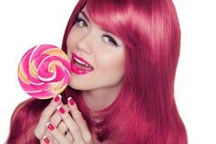 Muchacha adolescente sonriente feliz que sostiene la piruleta multicolora con rosa Imagen de archivo
