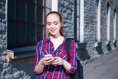 Muchacha adolescente sonriente hermosa del estudiante con el teléfono y la mochila Imágenes de archivo libres de regalías