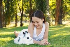 Muchacha adolescente sonriente hermosa linda que mira el conejo blanco-negro Imagen de archivo libre de regalías