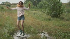 Muchacha adolescente sonriente hermosa que salta en charco muy fangoso en la carretera nacional metrajes