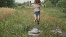 Muchacha adolescente sonriente hermosa que salta en charco muy fangoso en la carretera nacional almacen de metraje de vídeo