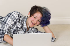 Muchacha adolescente sonriente mientras que usa su ordenador portátil y escucha la música Fotos de archivo