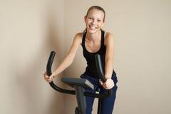 Muchacha adolescente sonriente que completa un ciclo en casa Imagen de archivo libre de regalías