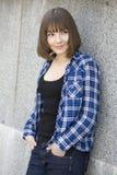 Muchacha adolescente sonriente que desgasta la camisa marcada con cuadros Imagen de archivo