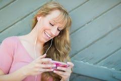 Muchacha adolescente sonriente que escucha la música en el teléfono elegante Imagenes de archivo