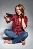 Muchacha adolescente sonriente que hace el autorretrato en su teléfono elegante Imagenes de archivo