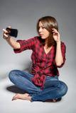 Muchacha adolescente sonriente que hace el autorretrato en su teléfono elegante Imagen de archivo libre de regalías