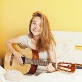 Muchacha adolescente sonriente que juega en la guitarra en la cama en casa Fotos de archivo libres de regalías