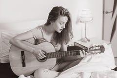 Muchacha adolescente sonriente que juega en la guitarra en la cama en casa Foto de archivo