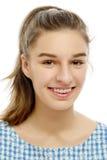 Muchacha adolescente sonriente que muestra apoyos dentales en blanco Fotografía de archivo