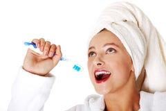 Muchacha adolescente sonriente que pone el cepillo de dientes a su boca. Fotos de archivo
