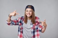 Muchacha adolescente sonriente que señala en sí misma Foto de archivo libre de regalías