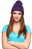 Muchacha adolescente sonriente que se coloca en sombrero Foto de archivo