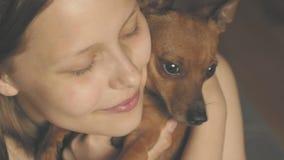 Muchacha adolescente sonriente que se divierte con su pequeño perrito del terrier de juguete 4k UHD almacen de video