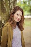 Muchacha adolescente sonriente que se inclina contra tronco de árbol Foto de archivo libre de regalías