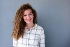 Muchacha adolescente sonriente que se opone a fondo gris Imagen de archivo
