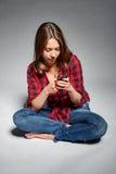 Muchacha adolescente sonriente que se sienta descalzo en el piso que sonríe en la cámara Foto de archivo libre de regalías