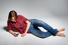 Muchacha adolescente sonriente que se sienta descalzo en el piso que sonríe en la cámara Foto de archivo