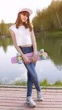 Muchacha adolescente sonriente que sostiene el monopatín Imagen de archivo