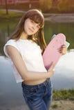 Muchacha adolescente sonriente que sostiene el monopatín Imagenes de archivo