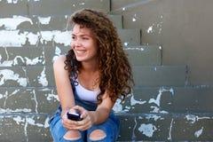 Muchacha adolescente sonriente que sostiene el teléfono y que se sienta en pasos Imágenes de archivo libres de regalías
