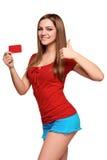 Muchacha adolescente sonriente que sostiene la tarjeta del crédito en blanco Imagenes de archivo