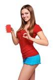Muchacha adolescente sonriente que sostiene la tarjeta del crédito en blanco Fotos de archivo libres de regalías