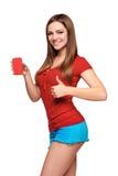 Muchacha adolescente sonriente que sostiene la tarjeta del crédito en blanco Fotos de archivo