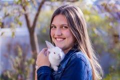 Muchacha adolescente sonriente que sostiene un conejo blanco del bebé al aire libre Imagen de archivo libre de regalías
