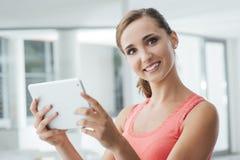 Muchacha adolescente sonriente que sostiene una tableta Imágenes de archivo libres de regalías