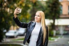 Muchacha adolescente sonriente que toma una foto del selfie en una ciudad urbana de la calle Imagen de archivo