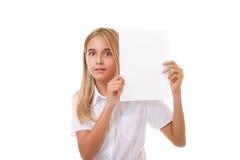 Muchacha adolescente sorprendida en la camisa blanca que sostiene el verraco de la muestra de publicidad Foto de archivo
