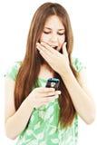 Muchacha adolescente sorprendida que mira el teléfono móvil Imágenes de archivo libres de regalías