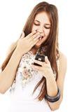 Muchacha adolescente sorprendida que mira el teléfono móvil Imagenes de archivo