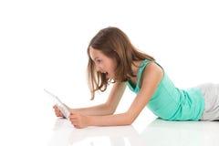 Muchacha adolescente sorprendida que usa la tableta digital Imagenes de archivo