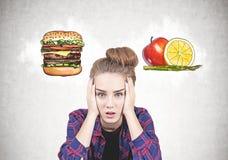 Muchacha adolescente subrayada con un bollo, opción de la comida Fotografía de archivo