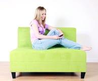 Muchacha adolescente texting en el sofá Fotos de archivo