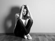 Muchacha adolescente triste en el suelo cerca de la pared. Foto de archivo