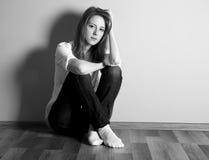 Muchacha adolescente triste en el suelo cerca de la pared. Imagen de archivo