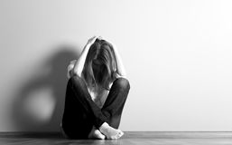 Muchacha adolescente triste en el suelo cerca de la pared. Fotos de archivo